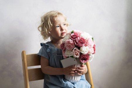 Photo pour Petite fille tenant un vase avec un grand bouquet de fleurs. Portrait de studio. - image libre de droit