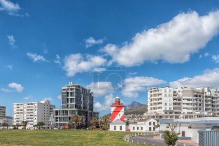 Photo pour CAPE TOWN, AFRIQUE DU SUD, LE 17 AOÛT 2018 : Le phare de Green Point à Mouille Point, au Cap, dans la province du Cap occidental. Immeubles et pic Devils sont visibles - image libre de droit