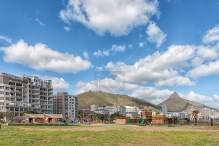Photo pour CAPE TOWN, AFRIQUE DU SUD, LE 17 AOÛT 2018 : Une aire de jeux pour enfants à Mouille Point, au Cap, dans la province du Cap occidental. Immeubles, Signal Hill et Lions Head sont visibles à l'arrière - image libre de droit
