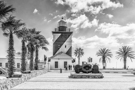 Photo pour CAPE TOWN, AFRIQUE DU SUD, LE 17 AOÛT 2018 : Le phare de Green Point à Mouille Point, au Cap, dans la province du Cap occidental. Un ancre de navires historiques et des gens sont visibles. Monochrome - image libre de droit
