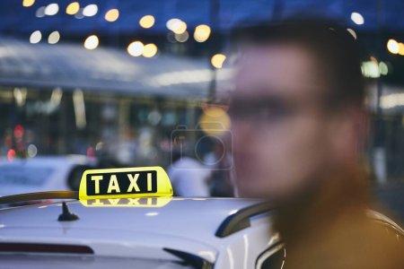 Photo pour Jeune homme en attente de taxi dans la rue pendant la nuit. Mise au point sélective sur l'enseigne de taxi. - image libre de droit