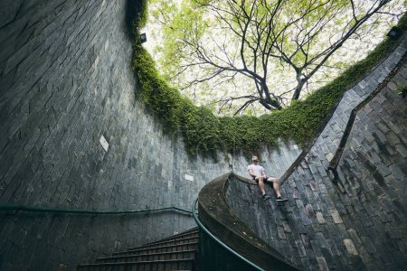 Lonely man sitting on the spiral staircase from underground walkway in Singapore.