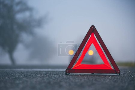 Photo for Traffic problem in thick fog. Car on the road behind warning triangle. - Royalty Free Image