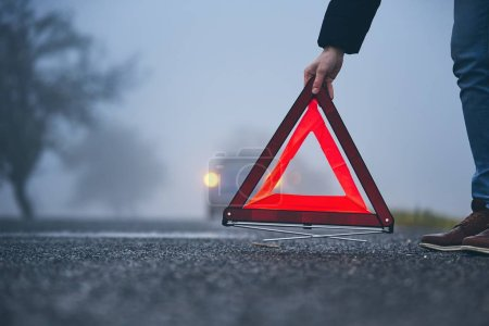Photo for Traffic problem in thick fog. Driver putting warning triangle behind his broken car. - Royalty Free Image