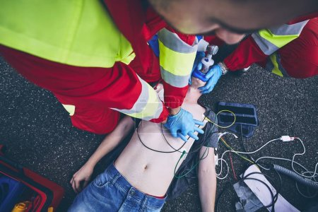 Photo for Cardiopulmonary resuscitation. Rescue team (doctor and a paramedic) resuscitating the man on the road. - Royalty Free Image