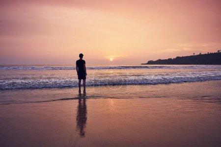 Photo pour Contemplation pendant le beau lever du soleil. Jeune homme sur une plage de sable idyllique près de Tangalle au Sri Lanka . - image libre de droit