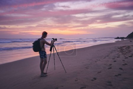Photo pour Young man photographing with tripod at beach after sunset. Photographer in blurred motion. - image libre de droit
