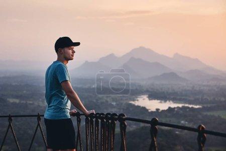 Photo pour Jeune homme de contemplation au coucher de soleil. Vue depuis le rocher de Sigiriya au Sri Lanka. - image libre de droit