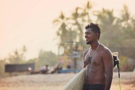 Photo pour Portrait de surfeur au coucher du soleil. Jeune homme tenant une planche de surf sur la plage. Tangalle, Sri Lanka . - image libre de droit