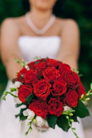 Photo for Bride woman showing bouquet of red roses flowers - Royalty Free Image