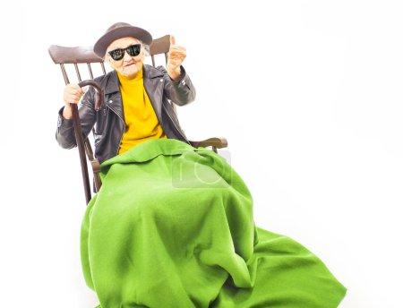 Photo pour Vieille femme avec chapeau et lunettes de soleil assis sur la couverture de chaise avec black vert . - image libre de droit
