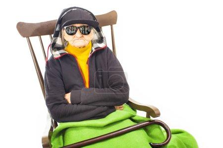 Photo pour Vieille femme avec chapeau et lunettes de soleil assis sur la chaise - image libre de droit