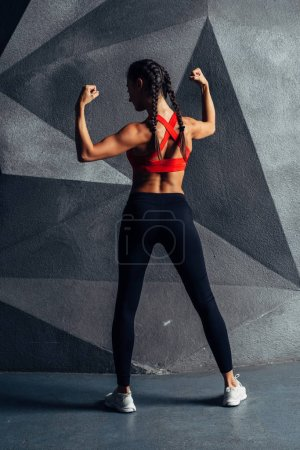 Photo for Back view portrait of a fitness woman showing biceps. - Royalty Free Image