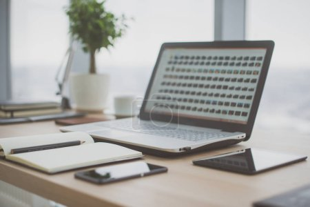 Foto de Lugar de trabajo con portátil portátil Cómoda mesa de trabajo en la oficina con ventanas y vistas a la ciudad - Imagen libre de derechos