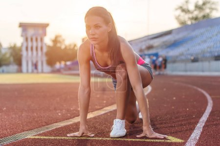 Photo for Women sprinters at starting position ready for race on racetrack - Royalty Free Image