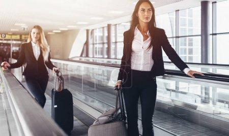 Photo pour Deux femmes confiantes portant des costumes formels debout sur une passerelle mobile à l'aéroport . - image libre de droit