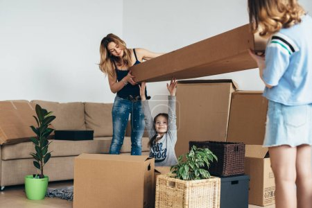 Photo for Family with cardboard boxes in new house at moving day. - Royalty Free Image