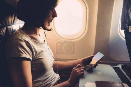 Photo pour Jeune femme sur un avion avec un smartphone dans ses mains. - image libre de droit