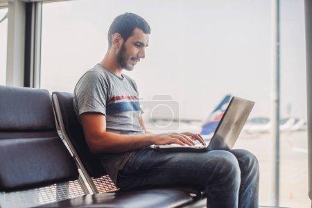 Photo pour Jeune homme utilisant un ordinateur portable dans le terminal de l'aéroport . - image libre de droit