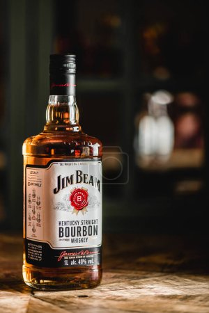 Photo for Jim Beam bourbon bottle on wooden table. Jim Beam is a famos brand of whiskey and the highest selling American bourbon in the world - Royalty Free Image