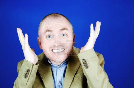 Photo pour L'homme étonné dans un manteau de crème jette vers le haut ses mains aux côtés sur un fond bleu. Copiez l'espace pour votre publicité, slogan ou promotion - image libre de droit