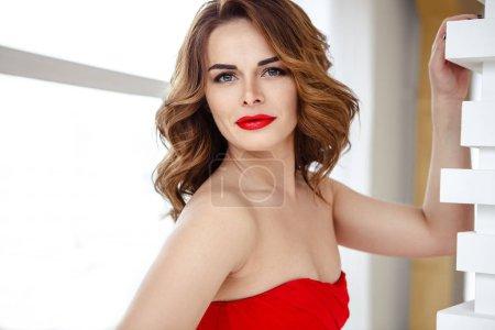 Photo pour Belle femme brune dans une robe rouge, portrait de beauté de mode avec maquillage et coiffure - image libre de droit