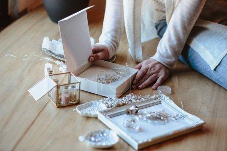 Photo pour Gros plan macro photo des détails, lieu de travail du décorateur et créateur de bijoux de mariage imitation. Les mains de la femme dans un processus de création - image libre de droit