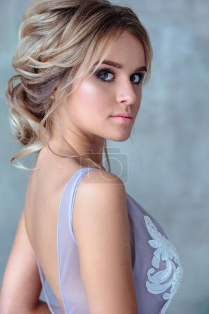 Photo for Bride blonde woman in a modern color wedding dress with elegant hair style and make up. Fashion beauty portrait over textured background - Royalty Free Image