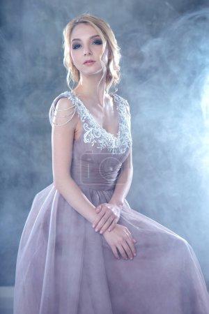 Photo pour Mariée femme blonde dans une robe de mariée de couleur moderne avec une coiffure élégante et le maquillage. Mode beauté portrait sur fond texturé - image libre de droit