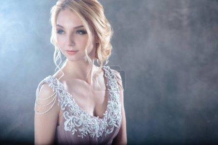 Photo pour Femme blonde de mariée dans une robe de mariage de couleur moderne avec le style de cheveux élégant et composent. Portrait de beauté de mode sur le fond texturé - image libre de droit