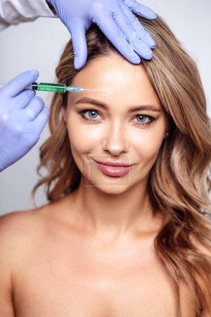 Photo pour Gros plan portrait de femme blonde avec des mains de cosmétologue près de son visage. Procédure en salon, spa et soins - image libre de droit