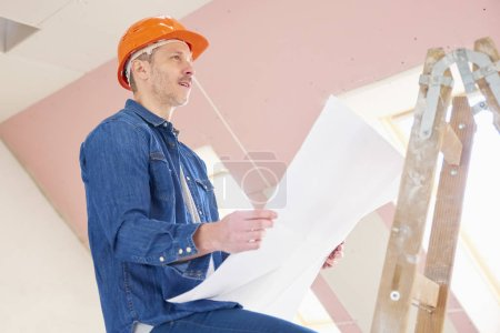Portrait of construction worker holding plan in his hand while standing on the ladder and working.