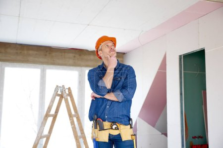 Portrait of thinking handyman standing with hand on his chin at the construction site.