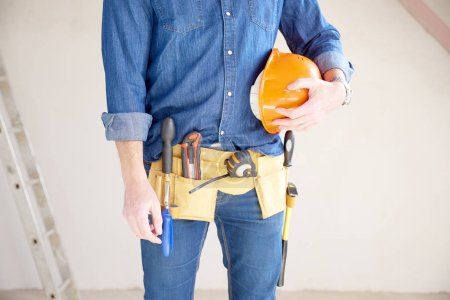 Cropped shot of a cunstruction man with handyman belt standing at construction site while holding safety helmet in his hand.