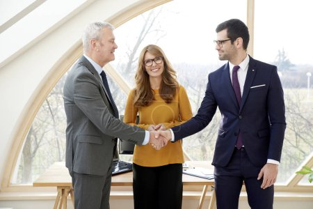 Senior businessman wearing suit and shaking hands with young businessman while stainding at the office with smiling businesswoman.