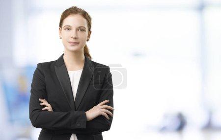 Foto de Disparo de un joven asistente financiero de pie en la oficina con los brazos cruzados . - Imagen libre de derechos