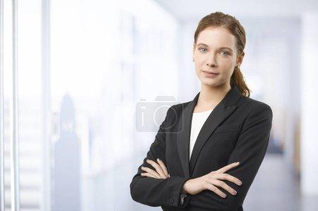 Photo pour Photo d'une femme d'affaires jeune souriant, debout dans le bureau avec les bras croisés. - image libre de droit