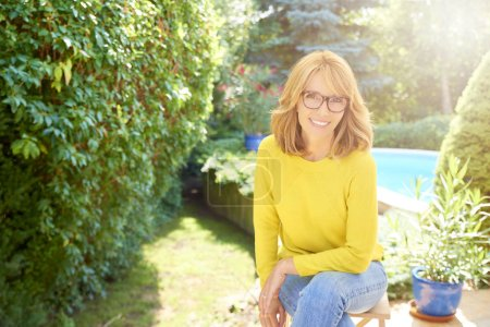 High angle shot of beautiful woman wearing sweater and jeans while sitting in the garden and relaxing.