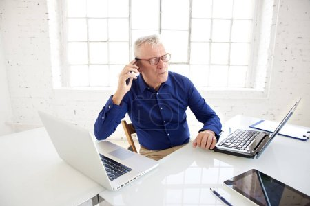 Photo pour High angle shot of senior businessman sitting at office desk behind his laptops and making call while working in the office. - image libre de droit