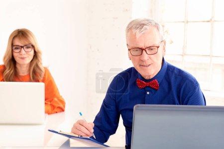 Foto de Tiro de hombre de negocios senior con corbata de lazo y gafas mientras usa el ordenador portátil en la oficina. Empresaria de mediana edad sentada detrás de él y trabajando en un cuaderno . - Imagen libre de derechos