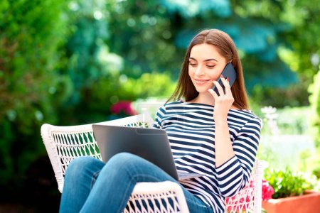 High angle shot of smiling young woman talking with somebody on her mobile phone and using laptop while working in the garden. Home office.