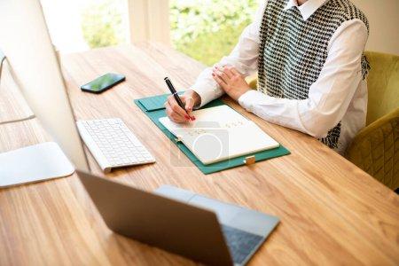 Photo pour Plan grand angle d'une femme d'affaires méconnaissable assise au bureau et écrivant quelque chose dans son carnet. - image libre de droit