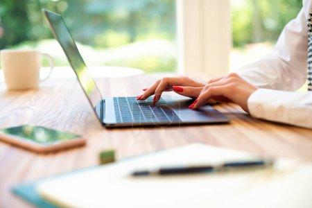 Photo pour Gros plan de la main d'une femme d'affaires en tapant sur le clavier d'un ordinateur portable. Femme d'affaires méconnaissable assise au bureau et travaillant sur un carnet. Bureau à domicile. - image libre de droit