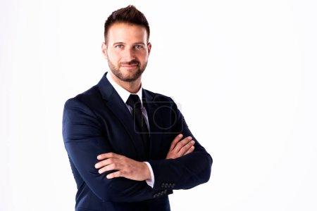 Photo pour Portrait d'un jeune homme d'affaires souriant portant un costume et debout les bras croisés tout en posant sur un fond blanc isolé. Espace de copie. - image libre de droit