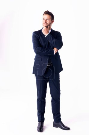 Photo pour Plan complet d'un bel homme d'affaires regardant attentivement tout en portant un costume et debout sur un fond blanc isolé. - image libre de droit
