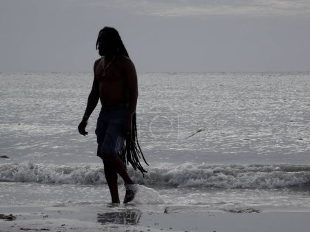 Photo for Ochos Rios, Saint Ann, Jamaica - 19th June 2017 : Silhouette picture of a Jamaican men walking out of the water on a beach near Ochos Rios, Jamaica - Royalty Free Image