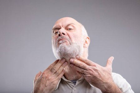 mature man checking for spots or if its beard is good enough to go out