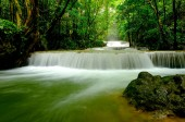 Multi-layered water fall with one rock in front of it in the forest of national park, Thailand.