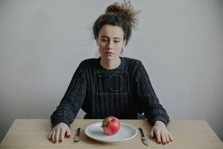 Photo for Sad woman looking on plate with red apple - Royalty Free Image