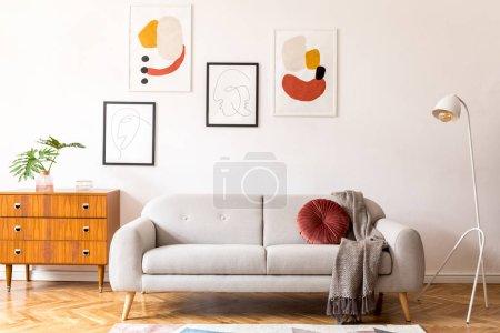 Photo pour Décor vintage élégant dans un intérieur plat spacieux avec canapé gris design, fauteuil, commode rétro et affiches sur le mur. Parquet en bois de Brwon, tapis élégant et plantes. Salon lumineux. - image libre de droit